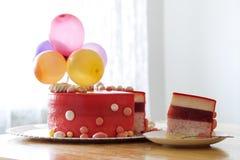 与空气baloons的自创红色生日蛋糕 切片一红色velv 免版税库存照片