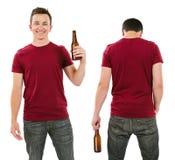 与空白的伯根地衬衣和饮用的啤酒的男性 免版税库存图片
