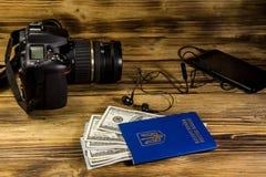 与空白的巧妙的电话、耳机、乌克兰护照、美元和照片照相机的旅行的概念在木书桌上 免版税图库摄影