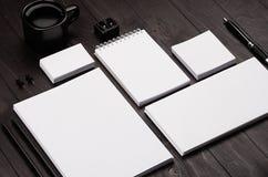 与空白的文具的现代minimalistic工作区在黑木板,顶视图,倾斜 免版税库存图片