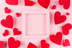 与空白的方形的框架的情人节背景和在柔和的桃红色颜色背景的红色纸心脏 库存图片