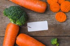 与空白的标记的新鲜的整个红萝卜在木板 免版税库存图片