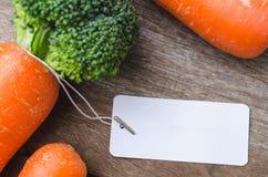 与空白的标记的新鲜的整个红萝卜在木板 免版税库存照片