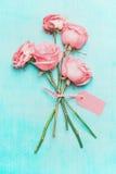 与空白的消息标志的浅粉红色的玫瑰束在绿松石背景,顶视图的文本的 免版税库存图片