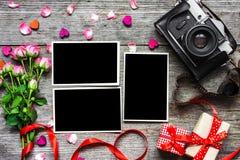 与空白的照片框架和桃红色玫瑰的葡萄酒减速火箭的照相机 库存图片