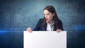 与空白的白板的惊奇的女商人画象在被隔绝的蓝色 与长的头发的女性模型 免版税图库摄影