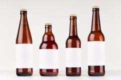 与空白的白色标签的布朗啤酒瓶汇集另外类型在白色木板,嘲笑  免版税库存图片