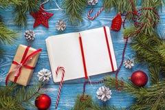 与空白的笔记本、冷杉分支、装饰和礼物盒的圣诞节背景 文本的空间 圣诞节计划目录 免版税库存图片