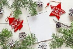 与空白的笔记本、冷杉分支和ornam的圣诞节背景 免版税库存图片