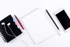 与空白的笔记本、巧妙的电话、耳机和其他办公用品的白色办公桌桌 顶视图 复制空间 平的位置 免版税库存图片