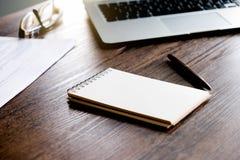 与空白的笔记本、笔、纸板料和膝上型计算机的办公室工作区在与温暖的秋天颜色和软焦点的木桌上 免版税库存图片