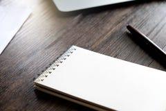 与空白的笔记本、笔、纸板料和膝上型计算机的办公室工作区在与温暖的秋天颜色和软焦点的木桌上 库存图片