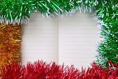 与空白的笔记本的圣诞节或新年装饰五颜六色的闪亮金属片框架您的文本的 免版税库存图片