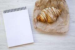 与空白的笔记本的新近地被烘烤的新月形面包在白色木tabl 图库摄影