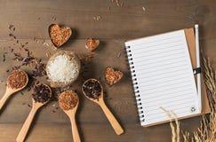 与空白的笔记本的米莓果,棕色和泰国红色混杂的米 免版税库存图片