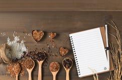与空白的笔记本的米莓果,棕色和泰国红色混杂的米 库存照片