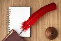 与空白的笔记的红色翎毛钢笔文本的 库存图片