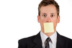 与空白的笔记的年轻商人关于他的嘴 免版税图库摄影
