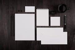 与空白的笔记薄、信头、名片、咖啡杯和耳机的黑暗的高雅工作空间在黑木板条背景 图库摄影
