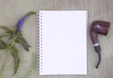 与空白的笔记薄和烟斗的大模型 空白纸 介绍的一个地方 在绿色被绘的木backgr的野花 免版税图库摄影