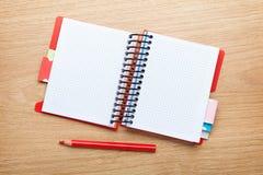 与空白的笔记薄和红色铅笔的办公室桌 库存图片