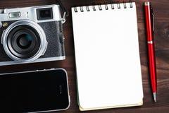 与空白的笔记薄页的经典照相机和在黑褐色木桌、葡萄酒桌与电话和绿色花上的红色笔 免版税库存图片