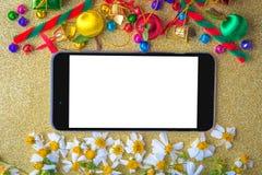 与空白的聪明的电话、礼物盒、雏菊花、糖果球和装饰的圣诞节和新年木背景横幅在金子 库存照片