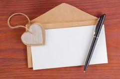 与空白纸的信封装饰了纸板心脏和笔在木桌上与空间文本的 库存图片
