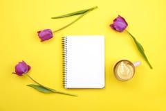 与空白纸笔记本的女性桌面构成,咖啡杯拿铁艺术,在黄色背景的郁金香花束 Girlie workplac 库存照片