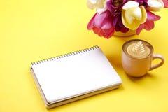 与空白纸笔记本的女性桌面构成,咖啡杯拿铁艺术,在黄色背景的郁金香花束 Girlie workplac 免版税库存照片
