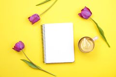 与空白纸笔记本的女性桌面构成,咖啡杯拿铁艺术,在黄色背景的郁金香花束 Girlie workplac 库存图片