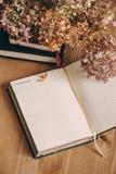 与空白页和干八仙花属的笔记本在木桌上 库存图片