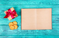 与空白页,一个礼物盒的一本开放书有弓和圣诞节曲奇饼的 以雪花和圣诞节礼物的形式曲奇饼 免版税库存图片