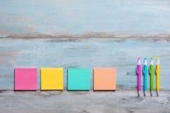 与空的五颜六色的稠粘的笔记的减速火箭的蓝色木桌 免版税库存图片