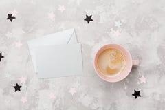与空的卡片和咖啡的信封在工作桌面看法的妇女的 平的位置 党邀请或问候消息 库存图片