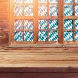 与空的木桌的慕尼黑啤酒节背景在窗口 免版税图库摄影