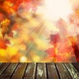 与空的木表,金黄Bokeh的秋天背景 免版税库存图片