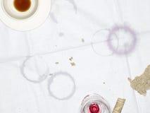 与空的杯和玻璃和湿气圆环的桌布 免版税库存照片
