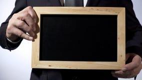 与空的空间您的文本的,拿着标志的商人的黑板模板 免版税库存图片