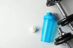 与空的蛋白质震动体育瓶的平的被放置的在桌上的构成和粉末 免版税库存照片