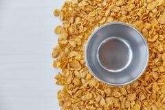 与空的金属碗的圆的框架标示用玉米片 在一张木桌上驱散的玉米片 自由空间为 图库摄影