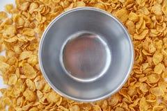 与空的金属碗的圆的框架标示用玉米片 在一张木桌上驱散的玉米片 免版税库存照片