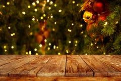 与空的黑暗的木甲板桌的圣诞节和新年背景在圣诞树和被弄脏的轻的bokeh 库存图片