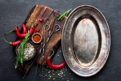 与空金属片和空间的烹饪背景文本的 平的位置结构的辣椒、迷迭香、香料和skewe 库存图片