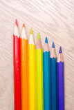 与空间的另外色的铅笔照片文本的 彩虹颜色七支铅笔在桌上说谎 Copyspace 回到学校 免版税库存图片