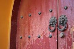 与突出的狮子敲门人的红色门 免版税库存图片