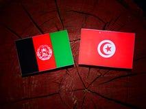 与突尼斯旗子的阿富汗旗子在被隔绝的树桩 免版税库存图片
