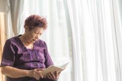 读与窗口光和葡萄酒的亚裔资深妇女一本书 免版税库存图片