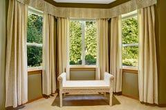 与窗口和柳条无背长椅的圆角落 免版税库存照片