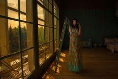 与窗口的美丽的女性画象 图库摄影
